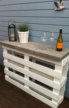 Two palettes. Three patio stones and some paint... A portable table for patio entertaining.  Cheap, easy and creatively pretty.