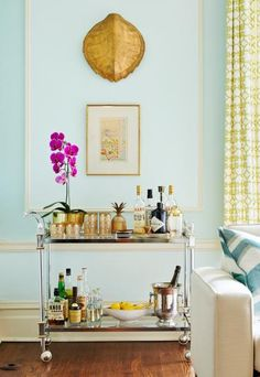 A neoclassical-style bar cart made by Maison Jensen, a turn-of-the-century French design firm, glitzes up a corner of the living room. More photos from this St. Louis home: http://www.midwestliving.com/homes/featured-homes/house-tour-balancing-act/?page=10