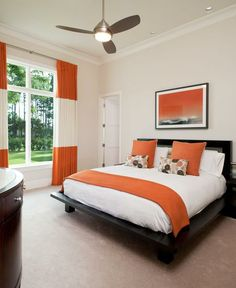 modern guest bedroom, dark wood furniture, light walls, orange accents, orange and white paneled drapws