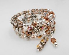 This silver and rose gold wrap bracelet is made on 4 rows of silver memory wire with an assortment of glass beads, bugle beads, Hematite, Czech fire polished beads, crystals, silver spacer beads, and finished off with 2 handmade crystal drops for a classy and elegant piece with just