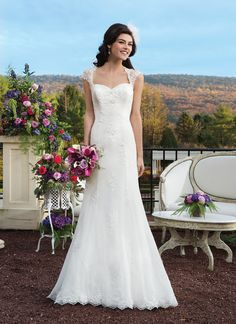 Chiffon and embroidered beaded lace fit and flare wedding gown which features a  Queen Anne neckline and delicate floating appliques throughout the  skirt.
