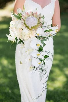 Fleur le Cordeur used white orchids, king proteas, peonies, and wispy greenery to create this softly striking cascading bouquet. | Photo by Tasha Seccombe | Planning and styling by Wedding Concepts