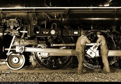 Two crewmen oil the running gear while 4-8-4 261 cools its heels in the siding.