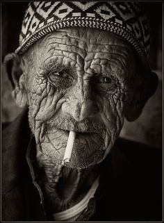 Years of history etched along his features. Enjoying a cigarette. I wonder the…