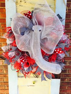 Show your Crimson pride with this unique mesh wreath!    This wreath is made out of red, white, and black mesh spirals. It also has houndstooth and red/white polka dot wired ribbon. In the center is an adorable elephant made out of silver mesh ribbon with google eyes and a houndstooth bow.    This wreath is constructed on a 16 wire work wreath and measures approx. 26 across.