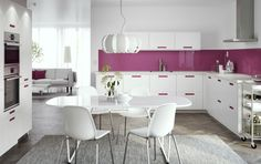 大きなホワイトのキッチンにピンクの取っ手とホワイトのワークトップ。ステンレススチールのレンジフード、オーブン、電子レンジも。