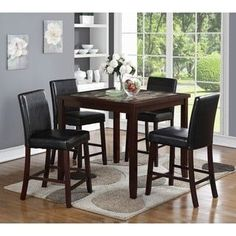 This pub dining room set is perfect for a small kitchen or breakfast nook. The set includes a counter height square table and four black padded chairs in a contemporary design. The faux marble tableto