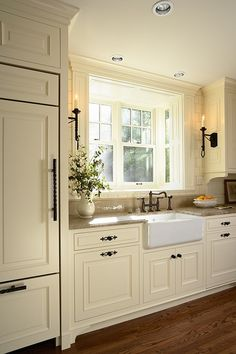 Antique white kitchen cabinets - See the before and after pictures of this farmhouse kitchen renovation with dark wood cabinets, quartz countertops and tile floors.
