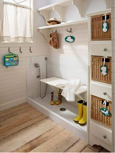 mudroom with shelving, hooks and basket storage plus a floor sink and hand shower. bh via Atticmag