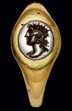 A ROMAN GOLD AND BLACK JASPER FINGER RING CIRCA 1ST CENTURY B.C.-1ST CENTURY A.D. The hollow ring with a plain hoop, round in section, tapering to an oval bezel set with a jasper engraved with a profile radiate draped bust of Alexander the Great wearing the horns of Ammon, his hair arranged in characteristic anastole, with unruly curls at the back of his head    Christie's