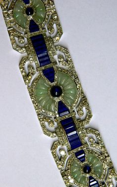 A Unique Art Deco Bracelet by Fouquet, circa 1925.  A unique bracelet manufactured during the Art Deco period by the prestigious French house Fouquet. The Bracelet presents an unusual combination of precious stones including old cut diamonds, sapphires, jade and lapis lazuli on the classic platinum mounting of the time.