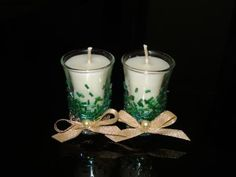 Hand poured candles in shot glasses decorated with green cylindrical beads with metallic finish, gold ribbons and pearls