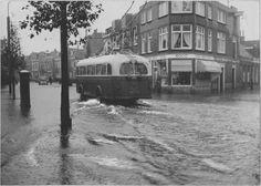 Groningen<br />De stad Groningen: De Meeuwerderweg met ernstige wateroverlast na hevige regenval. Met een trolleybus en de bekende winkel Manufacturen Roco Textiel t.h.v. de Martenstraat in1950