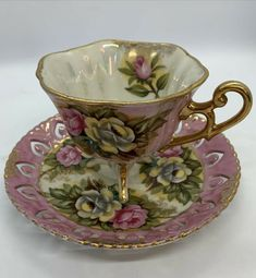 Beautiful Vintage Pedestal Tea Cup And Saucer decorated with rose and gold.