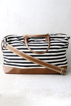 """Lulus Exclusive! Embrace a first class lifestyle with the Jet Setter Cream and Black Striped Weekender Bag! Cream and black striped canvas creates this large weekender bag with tan vegan leather handles and bottom. Unzip to reveal a spacious interior with two side pockets and one zipped side pocket. Carry from twin tote handles with a 7"""" drop or clip on the adjustable shoulder strap (measures 47"""" at longest)."""