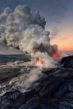 Lava meets the ocean producing huge billowing clouds of steam in Hawaii.