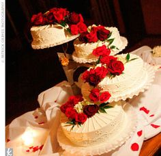 """The four-tier wedding cake alternated layers of chocolate and white cake with hazelnut filling. The layers were covered in a buttercream icing and decorated with a sunburst of icing """"pearls."""" The cake was topped by a cascade of red roses that spilled over the tiers.- love the cascading tiers design"""