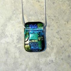 "Paula Woodward - This pendant is made from a patchwork of tiny pieces of Dichroic glass encapsulated in clear glass.   Shades of gold and green.   It is threaded on an 18"" Sterling silver snake chain, which threads through the pendant. £26"