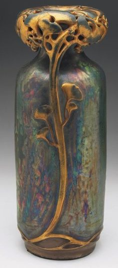 "Amphora vase, probably designed by Paul Dachsel, cylindrical shape under an iridescent green and blue glaze, elaborate gingko wreath at top with branches forming two handles, gold accents, marked, #0649, 5""w x 12.5""h"