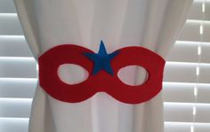 Tie back curtains with a superhero mask.