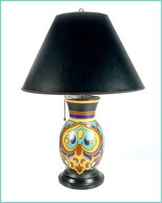 An exquisite 1920's art pottery lamp from the Gouda region of Holland.    Marvellous matte glaze in turquoise, navy, yellow and rust against a black background. The shade is contemporary. Image © Eclectisaurus. Visit our shop at 249 Gerrard St E, Toronto. 416-934-9009 www.eclectisaurus.com