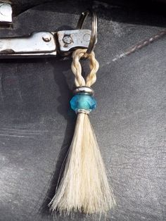 "The ""Julana"" style keychain features a 4-strand rope braid at the top of the keychain with decorative beading and charms. The bottom is a tassel that can be neatly trimmed or left in its natural state and resembling a real horse's tail."