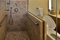 The walk-in shower has multiple grab bars, hand-held shower head and retractable bench seat to make it accessible. Photo by MosbyBuildingArts.com