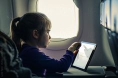 Girl using tablet on an airplane by Leslie Taylor #stocksy #realstock