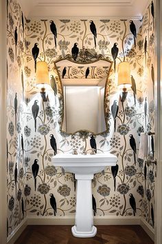 A powder room features hand-painted wallpaper from Au Fil des Couleurs.