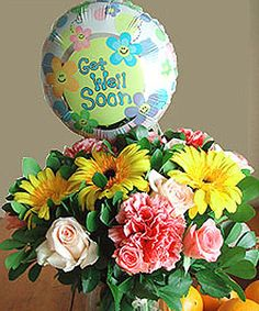 Gift Of Gladness  A blossoming bouquet that would bring gladness and cheer. Yellow and pink roses swirl among carnations and daisies to send a hearty message in a colorful balloon: Get Well! *Vase not included.