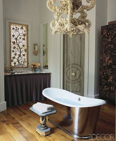 This master bath's tub-filler chandelier and laser-cut window panels are by Fisher Weisman; the tub and sink fittings are by Waterworks, and the Regency-style table is vintage.   - ELLEDecor.com