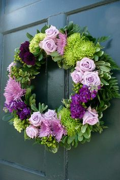 wedding wreath of green hydrangea, purple roses, green fugi mums - hung on the Church door to welocme the guests by Village Arts & Flowers
