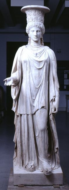 The so called 'Townley Caryatid', now in the British Museum, a Pentelic marble caryatid: a woman dressed to take part in religious rites. In a style adapted from Athenian work of the 5th century BCE. One of a group of five surviving caryatids found at the site, arranged to form a colonnade in a Sanctuary, most probably of Demeter (also Isis has been suggested, cf. Cook 2011, nr. 264: 'A Statue of Isis, six feet six inches high; upon the head is the calyx of the Lotus, the symbol of this…