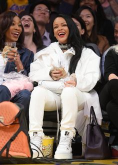 "Rihanna looks fierce in an all-white ensemble while attending the Lakers game held at the Staples Center on Sunday (March 6) in Los Angeles. The 28-year-old ""Work"" entertainer sat courtside as she watched the home team beat the Golden State Warriors"