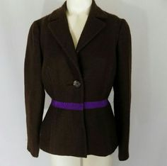 Prada Brown Wool Purple Grosgrain Trim Jacket Stunning dark brown jacket with purple grosgrain ribbon trim by Prada. Classic jacket/casual blazer styling; collar and lapels, semi-formed shoulders, v neckline, single button closure with hidden internal snap closures, purple grosgrain ribbon detail at waist, and a double-vented rear. Seaming/tailoring. Marked size 40, equivalent to US size 4. 100% wool, lined. Made in Italy. Excellent condition with no noted flaws; one interior snap may need…