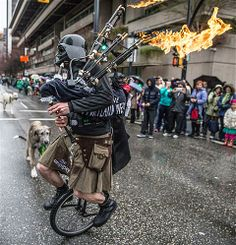 Image: A St. Patrick's Day Parade rides a unicycle while wearing a Darth Vader mask and playing bagpipes that shoot fire, in Vancouver, Cana...