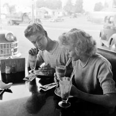 1950s teenage couple order milkshakes and burgers at a local San Diego Diner