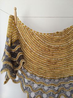 This top down shawl starts with easy two-color garter stitch. The simple semi-circular stripes are followed by a large lace pattern. The holes increase in size while adding stitches to form a scallope                                                                                                                                                                                 More