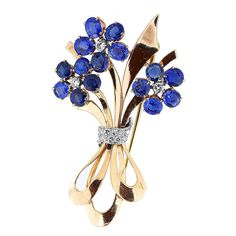 Sapphire Diamond Gold Floral Brooch. Two tone 14 karat yellow and white gold vintage floral pin set with 15 oval shape MONTANA blue sapphires set with full cut diamonds accents. 20th century