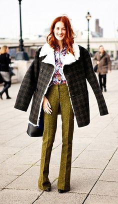 Taylor Tomasi-Hill wears a floral blouse, skinny flare trousers, and a fur-lined plaid coat