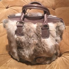 Fur handbag by Entra, imported from Italy Brand new fur handbag by Italian designer Entra. Leather is super soft taupe with silver metal accents. Interior is brown with one open compartment and one side zippered pocket. Bottom is trimmed in leather with silver metal feet. Looks like there is a scratch on the bottom but it's not torn or anything and has never been used so might be part of the leather. Sorry no trades Entra Bags