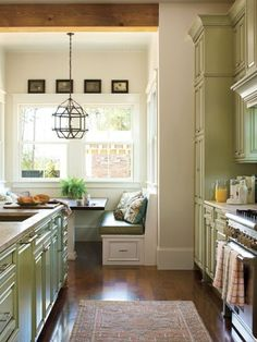 Warm wood floors, green cabinets, and banquet seating.