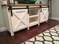 A TV stand with barn doors and shelves.