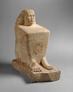 """Ankhwennefer is shown squatting on the ground. Only the head, hands and feet emerge from a cloak that he has drawn tightly around his body. Since the Middle Kingdom this statuary type, called a """"block statue,"""" served to represent non-royal persons in a general context of solar beliefs"""