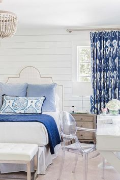 White and blue bedroom boasts shiplap walls lined with a white grid nailhead headboard on bed dressed in white and blue bedding placed next to a gray French nightstand and a glass lamp placed under a window dressed in blue ikat curtains, Bansuri Iris Fabric.