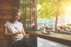 Charming woman with beautiful smile reading good news on mobile phone during rest in coffee shop, happy Caucasian female watching her photos on cell telephone while relaxing in cafe during free time ,