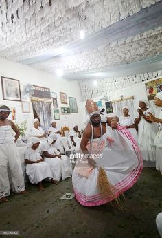 A worshipper dances dressed as the goddess Iansa after falling into a trance during a Candomble ceremony on August 17, 2014 in Cachoeira, Brazil. Candomble is an Afro-Brazilian religion whose practitioners often fall into trances during ceremonies and believe they have become possessed by gods, or orixas. The roots of the religion came to Brazil via African slaves while eventually incorporating elements of Catholicism. The state of Bahia received at least 1.2 million slaves from Africa and…