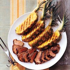 FOURTH OF JULY BBQ:  Hawaii: The Island State is known for its luscious, golden pineapples, which hold a place of honor in this Asian-influenced grilled pork dish. When choosing a pineapple, pick one with a deep, sweet fragrance.  Recipe: Hoisin-Honey-Glazed Pork Tenderloin with Grilled Pineapple  Serve with: Green Papaya Salad   - Delish.com