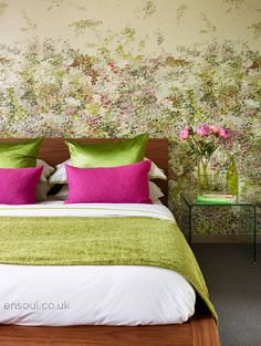 Guest bedroom featuring hot pink and green. Beautiful impressionist art style wallpaper is the inspiration matched perfectly with a walnut bed and glass bedside tables so as not to obscure the paper.