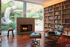 "Architect Margaret Griffin, in collaboration with architect Elyse Grinstein, renovated a home on Los Angeles's West Side, an area that has natural creeks and groves of indigenous trees. The star tree here is a 300-year-old sycamore that shades a small spring and lush slope in back. The snug library ""started out with a full brick wall facing the tree,"" explains the owner, but the brick was replaced by sheets of glass to bridge the room's connection to the outdoors."